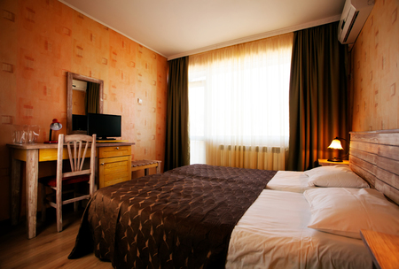 Warm colored light in bedroom at hotel Stock Photo