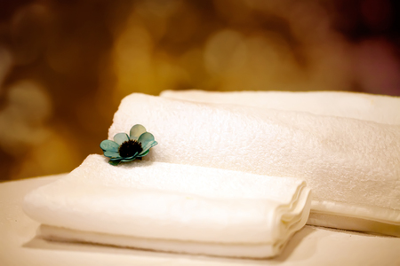 Spa towels in wicker basket on dark background