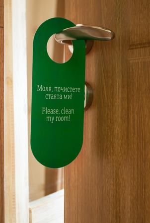 Hotel hanger sign, door knob. Do not disturb. Please clean up the room.