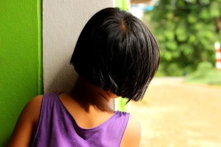 envelop: Behind of girl who try to hide herself at corner of green house and she looking forward on the soil road.