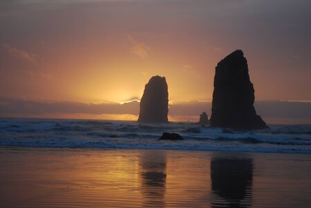 sunset behind coastal rock formations photo