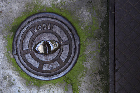 small manhole cover on a damp concrete floor Stock Photo