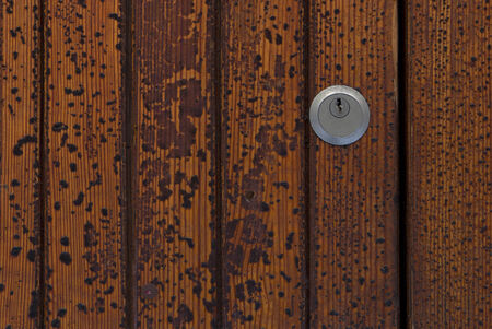 detail of keyhole on old wooden door with peeling paint texture
