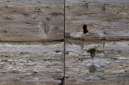 detail of decaying wooden door with keyhole, nails and texture of rotten wood with wormholes Stock Photo