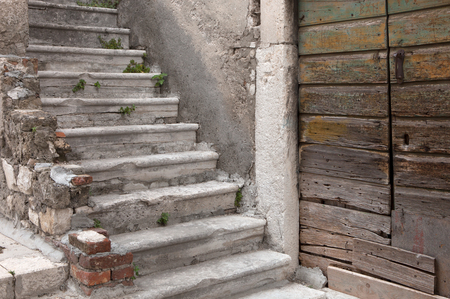 decaying stairway and door of abandoned mediterranean house