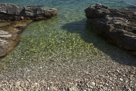 small beach with pebbles on entrance to crystal clear sea