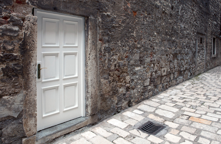 new white door on old dirty wall in narrow paved street