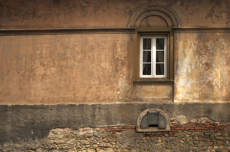 windows with arch relief on forgotten empty wall painted with many layers of fading warm tones