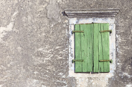 wooden green window on aged plastered wall