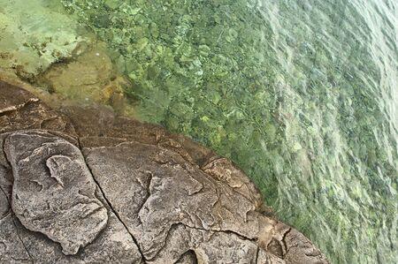 seashore stone and shallow clear sea