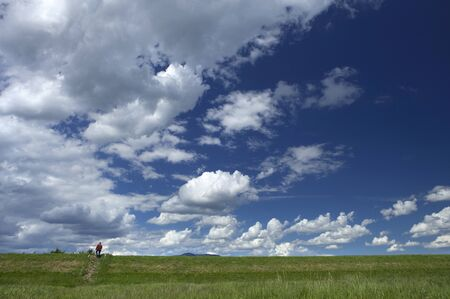 tiny insignificant red human figure contrasting vast cloudy blue sky expanse Stock Photo