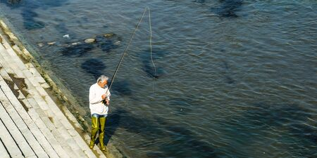 Adult man fishing in the river Vardar in Skopje
