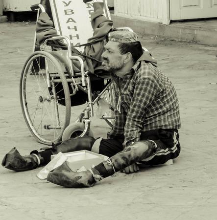 Erwachsenen Mann sitzt auf dem Boden neben einem Rollstuhl Seine Beine sind in Gummi gebunden, und er kann nicht gehen wird er um Gnade von den Menschen zu Fu� um ihn herum Editorial