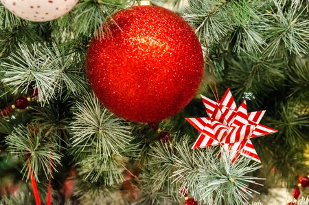 Weihnachtskugel mit rotem Farbband auf einem Weihnachtsbaum Lizenzfreie Bilder