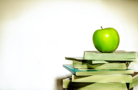 Gr�ner Apfel und B�cher, die isoliert auf wei�em Hintergrund
