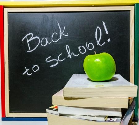 Blackboard, auf dem geschrieben steht:, zur�ck in die Schule, mit gr�nem Apfel und B�cher vor ihm