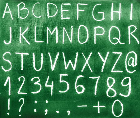 The alphabet,numbers and punctuation written with chalk on a green board  photo