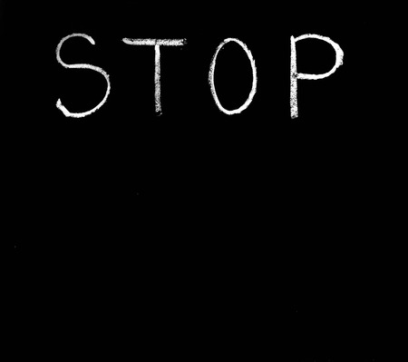 Single word ,,STOP,,written with chalk on a black background  photo