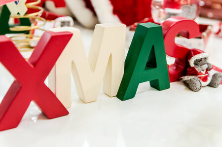 Single word,, XMAS,,made of diferent colored wooden letters with small Teddy bear next to it  photo