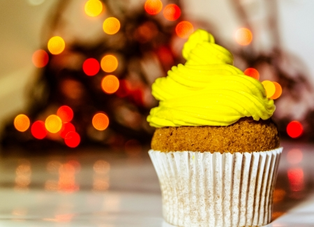 Yellow cream cupcake with blury lights in the background