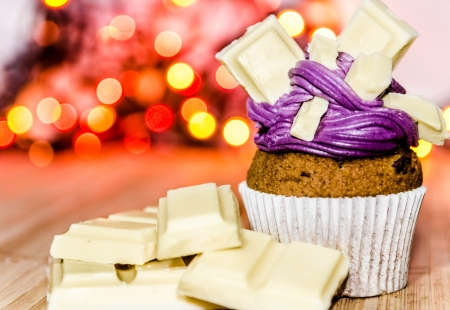 Cupcake with violet cream and white chocolate photo