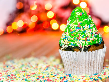 Tree cupcake with green cream and colorful crumbs on top of it