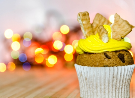 Yellow cream cupcake with bisquits on top of it