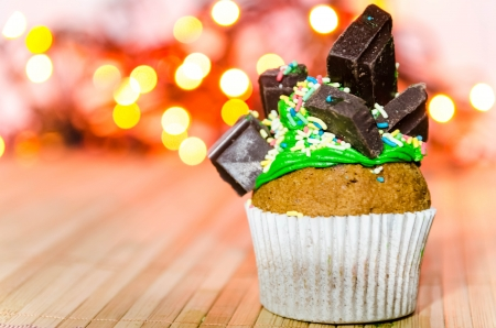 Cupcake with green cream and white chocolate on top of it