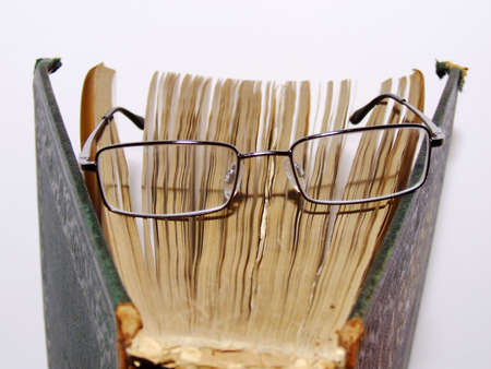 glasses on open book closeup photo