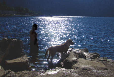 man and a dog looking at the sea photo