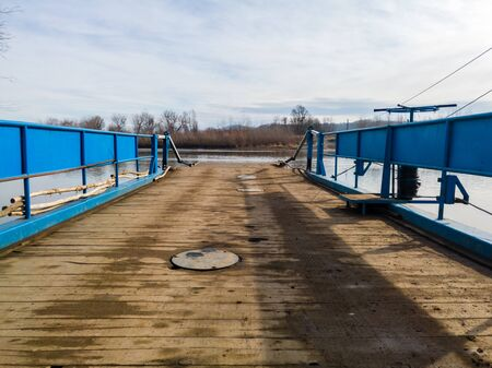 Ferry for transporting goods and people across the river moored along the river bank with a lowered ramp ready for loading. Raft made of metal with metal fences and wooden floor.