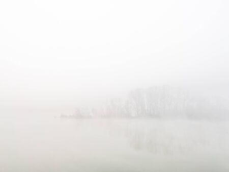 A cold autumn morning with a thick fog and a mystical river island that disappears behind a veil of mist together with a small grove of deciduous trees of branches pointing towards the sky.