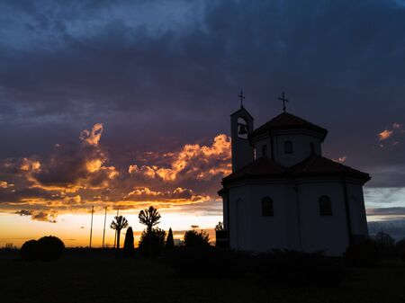 A religious building in the countryside against colorful clouds at sunset. Church of the Holy Apostles Peter and Paul near Brod, Bosnia and Herzegovina.
