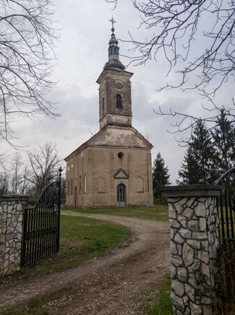 An old abandoned church building in a dilapidated condition against a gloomy sky during the cloudy day. Cracked and peeled facade on religious building.