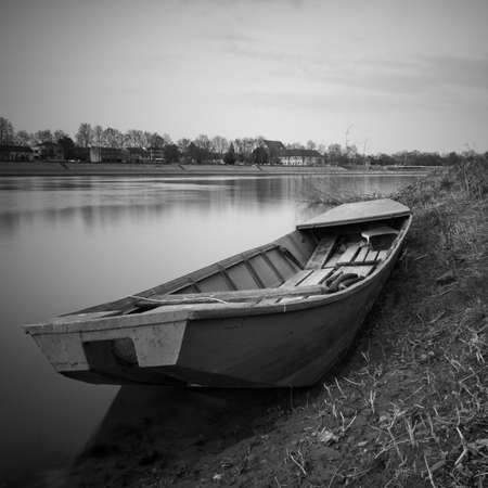 An old fishing boat stranded on the bank of the Sava River in Bosanski Brod, Bosnia and Herzegovina. Black and white picture of a boat in the mud by the river.