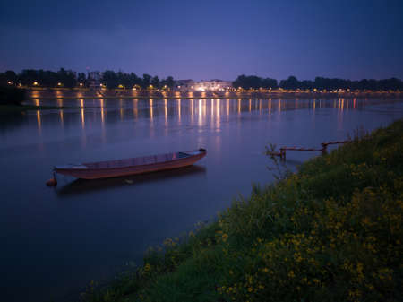 Quiet landscape of the Sava river with an anchored fishing boat near the wooden dock and Slavosnki Brod in the background during cloudy dusk Stock Photo