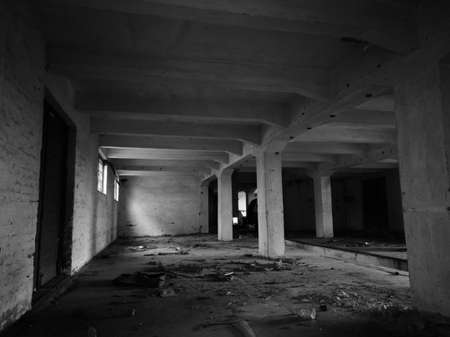 Inside an abandoned concrete building, an old messy industrial warehouse with small windows and large doors during the day.