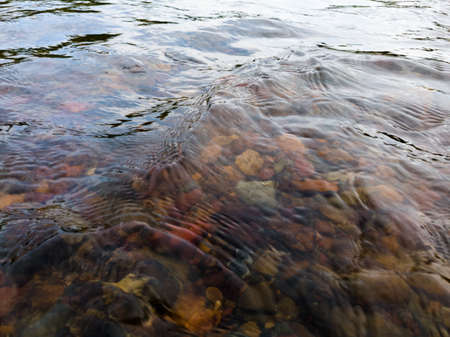Wavy surface of water on shallow rapid stream with colorful gravel at bottom, running water in creek, intimate landscape