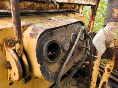 Interior of cabin with levers and instruments panel of abandoned deserted old rusty bulldozer, vintage industrial heavy machine, earthmover equipment, scrap metal Banque d'images
