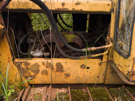 Abandoned old rusty bulldozer with diesel motor and hydraulic hose, vintage industrial heavy machine, earthmover equipment, tracked vehicle Banque d'images