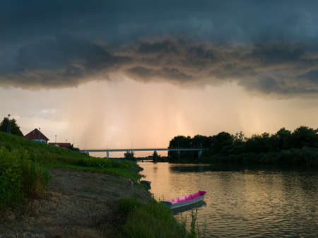 Storm arcus shaft and cumulonimbus cloud with heavy rain or summer shower, severe weather and sun glow behind rain. Landscape with Sava river with moored boats along grassy river bank and bridge.
