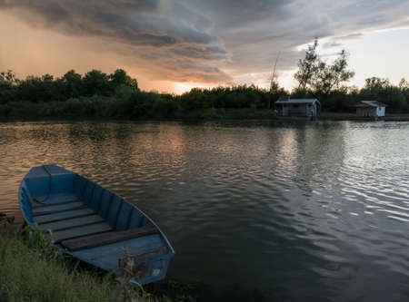 Storm arcus shaft and cumulonimbus cloud with heavy rain or summer shower, severe weather and sun glow behind rain. Landscape with Sava river with moored boat along grassy river bank and hut.