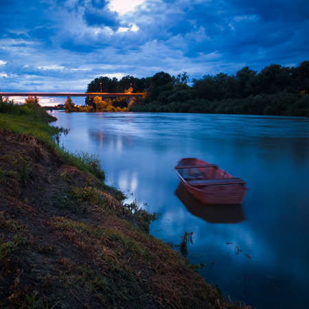 Cloud overcast evening during blue hour. Landscape with Sava river, moored fishing boat along grassy river bank and bridge in Bosanski Brod, Bosnia and Herzegovina
