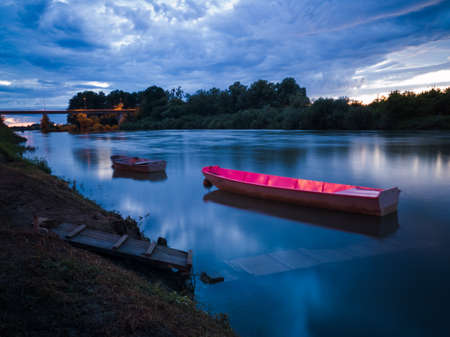 Cloud overcast evening during blue hour. Landscape with Sava river, moored fishing boats near wooden dock and bridge in Bosanski Brod, Bosnia and Herzegovina 写真素材