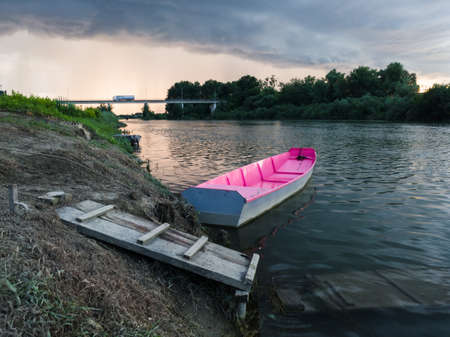 Storm arcus shaft and cumulonimbus cloud with heavy rain or summer shower, severe weather and sun glow behind rain. Landscape with Sava river with moored boat next to wooden dock and bridge.