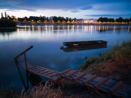 Cloud overcast evening during blue hour. Landscape with Sava river, cityscape, moored fishing boat near wooden dock in Bosanski Brod, Bosnia and Herzegovina
