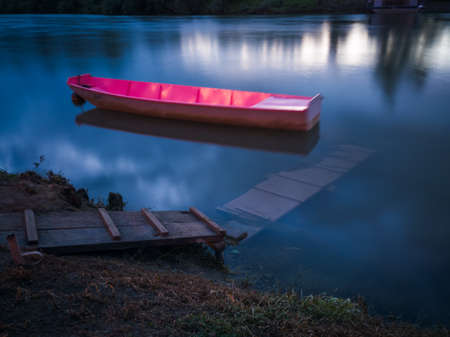 Intimate landscape with flooded wooden dock and moored fishing boat along grassy riverbank during overcast blue hour. 写真素材