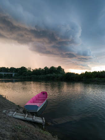 Storm arcus shaft and cumulonimbus cloud with heavy rain or summer shower, severe weather and sun glow behind rain. Landscape with Sava river with moored boat next to wooden dock during stormy evening