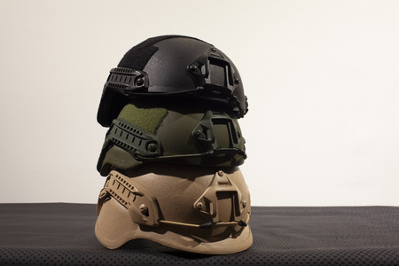 Three military helmets on white background Imagens