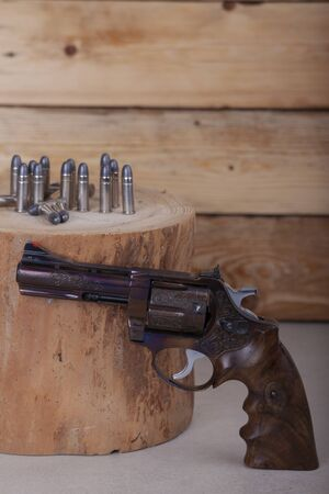 old style revolver handgun photographed on the wooden background
